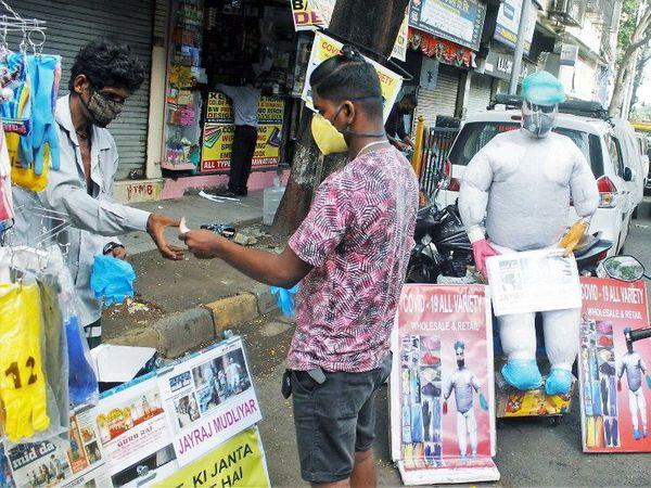 मुंबईत अनलॉक झाल्यानंतर आता रस्त्यांवरील दुकानेही सुरू झाली आहेत. दुकानातून मास्क विकत घेताना एक माणूस. - Divya Marathi