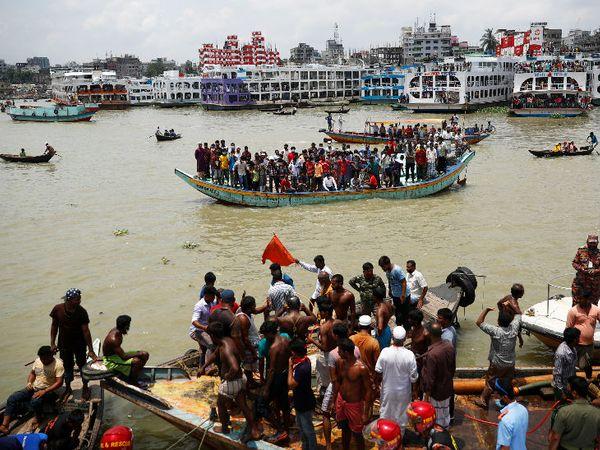 ढाका येथील बुढीगंगा नदीवर अपघातानंतर लोक जमा झाले. दुसर्या बोटीला धडक बसल्यामुळे हा अपघात झाला.