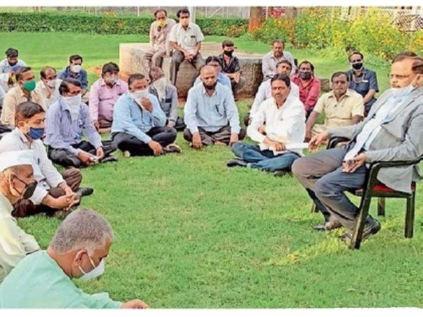 विद्यापीठ परिसरातील हिरवळीवर आंदाेलन करणाऱ्या कर्मचाऱ्यांशी चर्चा करताना कुलगुरू डाॅ. प्रमाेद येवले. - Divya Marathi