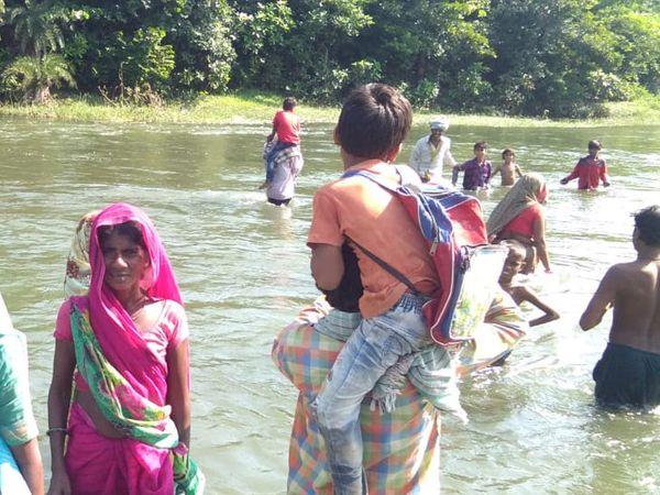 બાળકોને ખભે બેસાડીને શાળાએ મૂકવા જવું પડે છે - Divya Bhaskar
