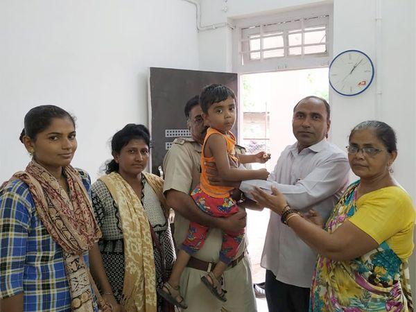 બાળકને દાદા-દાદીને સોંપી રહેલી બાપુનગર પોલીસ - Divya Bhaskar