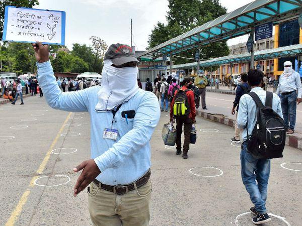 જબલપુર બસ સ્ટેશન પર સરકારી કર્મચારી મહારાષ્ટ્રથી પરત ફરેલા શ્રમિકોને સોશિયલ ડિસ્ટન્સિંગનું પાલન કરી ઉભા રહેવા સૂચન કરી રહ્યા છે