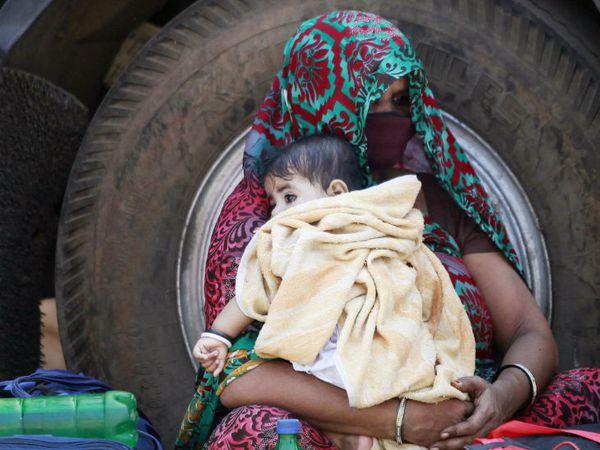 મુંબઈની ધારાવીમાં આ મહિલા રેલવે સ્ટેશન જવા માટે બસની રાહ જોઈ રહી છે