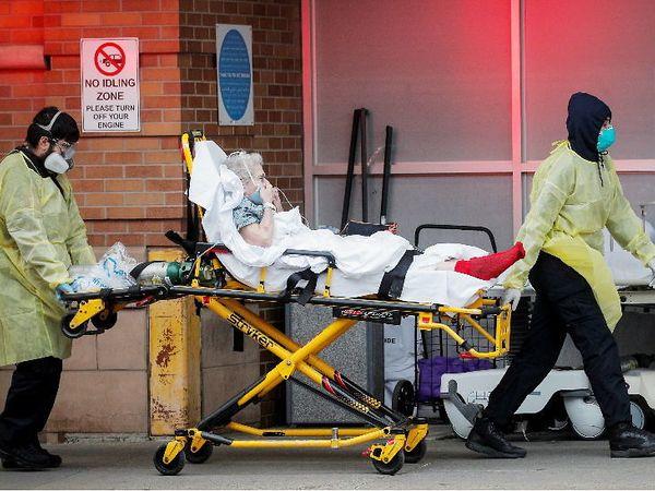 આ તસવીર ન્યૂયોર્ક શહેરની છે. કોરોના સંક્રમિતને હોસ્પિટલમાં લઈ જઈ રહેલા સ્વાસ્થ્ય કર્મચારી.