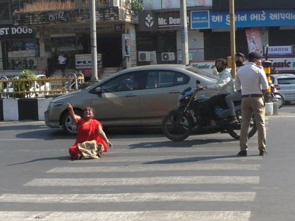 રસ્તા પર બેસી જઈને મહિલાએ રાડારાડ કરી હોબાળો મચાવતાં તેને પોલીસ સ્ટેશને લઈ જવાઈ હતી. - Divya Bhaskar