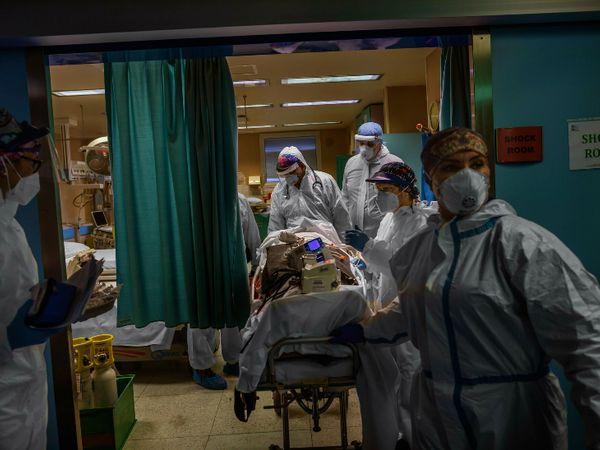 શુક્રવારે ઈટાલીમાં બોગલિન શહેરની એક હોસ્પિટલમાં ગંભીર દર્દીને ICUમાં શિફ્ટ કરતો સ્ટાફ.
