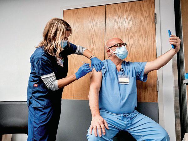 વેક્સિનવાળી સેલ્ફી : અમેરિકામાં વેક્સિન લગાવતી વખતે સેલ્ફી લેતા વૃદ્ધ. - Divya Bhaskar