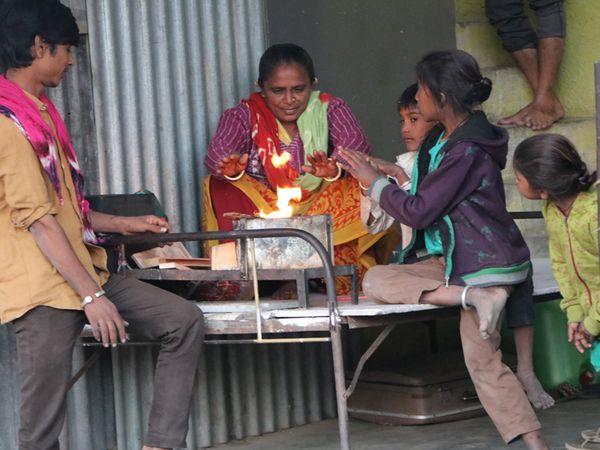 એરપોર્ટ રોડ પર એક પરિવારે ફળિયામાં પલંગ પર તાપણું કરી ઠંડીથી રક્ષણ મેળવ્યું હતું. - Divya Bhaskar