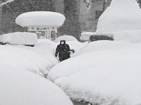 જાપાનના ટોયોમા વિસ્તારમાં બરફના થર વચ્ચેથી પસાર થતી મહિલા. આ વિસ્તારમાં સેંકડો વાહનો બરફના કારણે અટવાઈ પડ્યા છે. આ ઉપરાંત વિમાન અને ટ્રેન સેવાઓને પણ અસર થઈ છે.