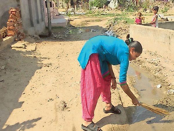 વોર્ડ 7માં અનેક સોસાયટીઓમાં ભૂગર્ભ ગટરના દૂષિત પાણી વર્ષોથી રોડ પર રેલાય છે. મહિલાઓ જાતેજ પોતાના ઘર આગળ રોડની સફાઈ કરે છે. - Divya Bhaskar