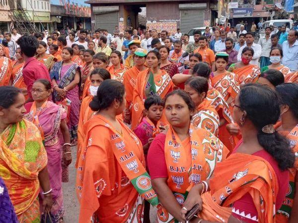 भाजपा के लोगो के साथ भगवा साड़ी पहने महिलाएं।