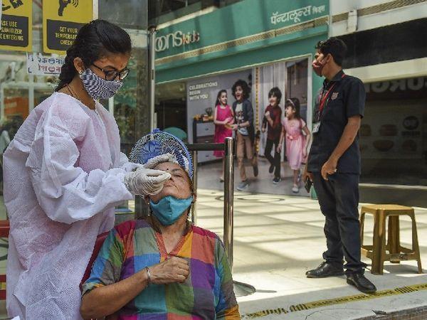 मुंबई के एक मॉल के बाहर परीक्षण के लिए नमूना लेते बीएमसी स्वास्थ्य कार्यकर्ता।