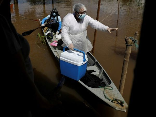 एक स्वास्थ्य कार्यकर्ता ब्राजील के अमेज़ॅन राज्य के अनामा में नदी के पार एक कोरोना रोगी का इलाज करता है।