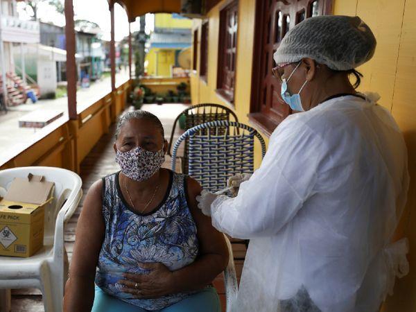 બ્રાઝિલમાં કોરોનાથી ખરાબ પરિસ્થિતિ વચ્ચે ઘરે ઘરે જઈને કોરોના વેક્સિન લગાવવામાં આવી રહી છે. આ દરમિયાન એક મહિલાને તેના ઘરની બહાર જ ચીનની વેક્સિન સિનોવૈક લાગવતી એક હેલ્થકેર કાર્યકર.