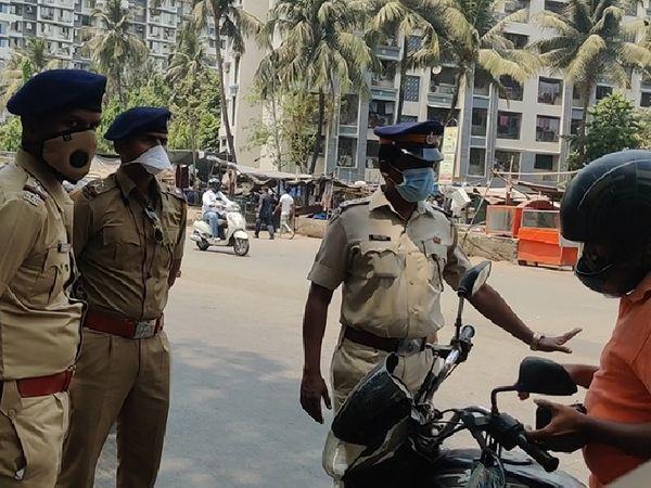 मुंबई के कुर्ला पूर्व क्षेत्र में लोगों की जाँच करते पुलिसकर्मी।
