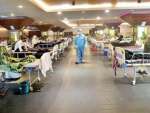 નવી દિલ્હીના બેન્ક્વિટ હોલમાં બનેલી હોસ્પિટલમાં દાખલ દર્દીઓને જોઈ રહેલા ડૉક્ટર. - Divya Bhaskar