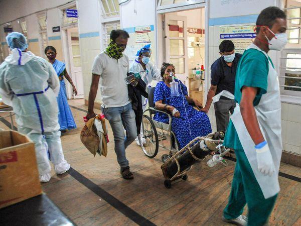આ ફોટો બેંગલુરુનો છે. અહીં ઓક્સિજન સપોર્ટ સાથે એક કોરોનાના દર્દીને હોસ્પિટલમાં દાખલ કરવા માટે લઈ જતાં હેલ્થકેર વર્કર્સ.