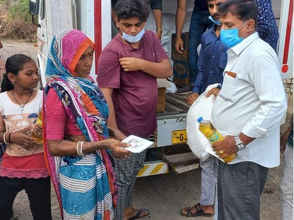 રાશન કિટ મેળવી રહેલો પરિવાર - Divya Bhaskar