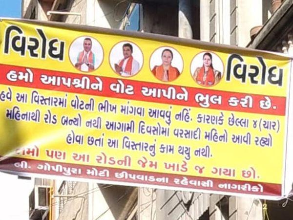 ખરાબ રસ્તાને લઈ સ્થાનિકોએ બેનર લગાવી નગરસેવકોનો વિરોધ કર્યો હતો - Divya Bhaskar