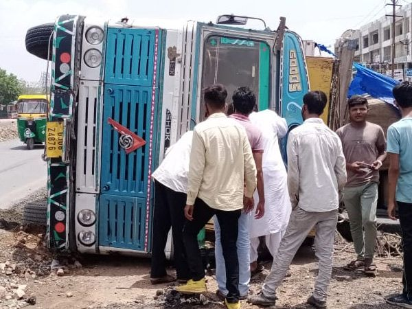 ટ્રક પલટી જતા માલ સામાન રોડ ઉપર વેરવિખેર થઇ ગયો હતો. - Divya Bhaskar