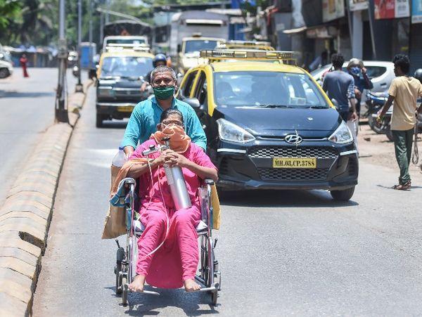 मुंबई के धारावी में एक शख्स अपनी पत्नी को व्हील चेयर पर बैठा कर हॉस्पिटल तक ले जाता हुआ।