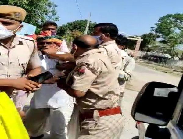 मारपीट के दौरान वृद्ध का मुंह पकड़े हुए पुलिसकर्मी।