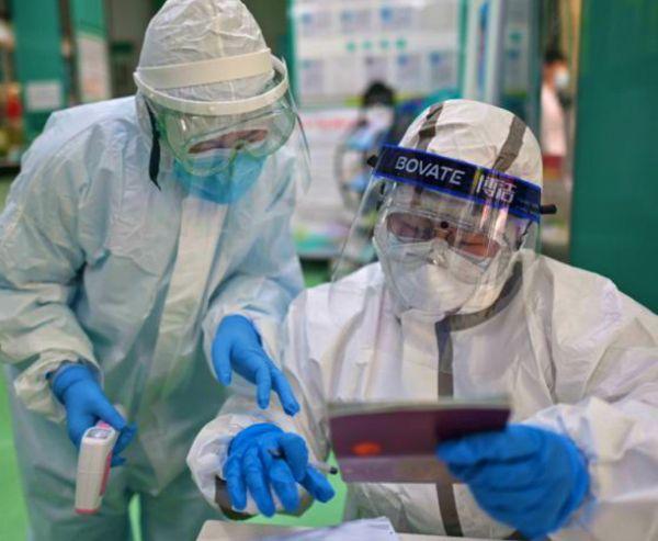 वुहान के एक अस्पताल में संक्रमित की रिपोर्ट देखता मेडिकल स्टाफ। शहर में करीब 45 दिन बाद नया मामला सामने आया है। लोकल एडमिनिस्ट्रेशन ने इसकी पुष्टि की।