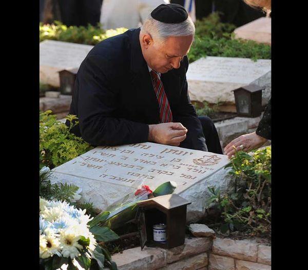 बेंजामिन नेतन्याहू अपने भाई की कब्र के पास बैठे हैं।  उनका कहना है कि ऑपरेशन थंडरबोल्ड की मौत और उनके भाई ने उनकी जिंदगी बदल दी (फाइल फोटो)