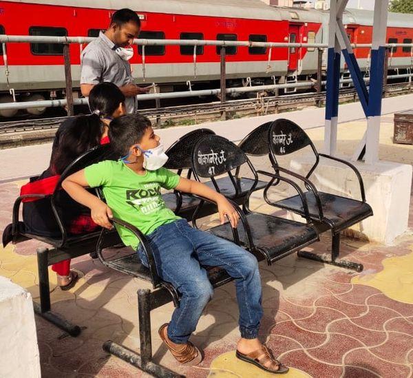 परिवार के साथ रेलवे स्टेशन पर है, लेकिन मास्क को सिर्फ लटकाकर रखा है।