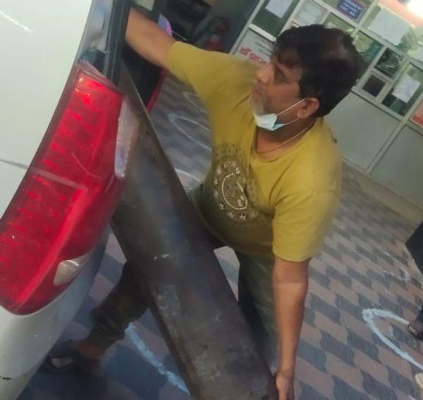 गाड़ी में सिलेंडर रखता युवक।