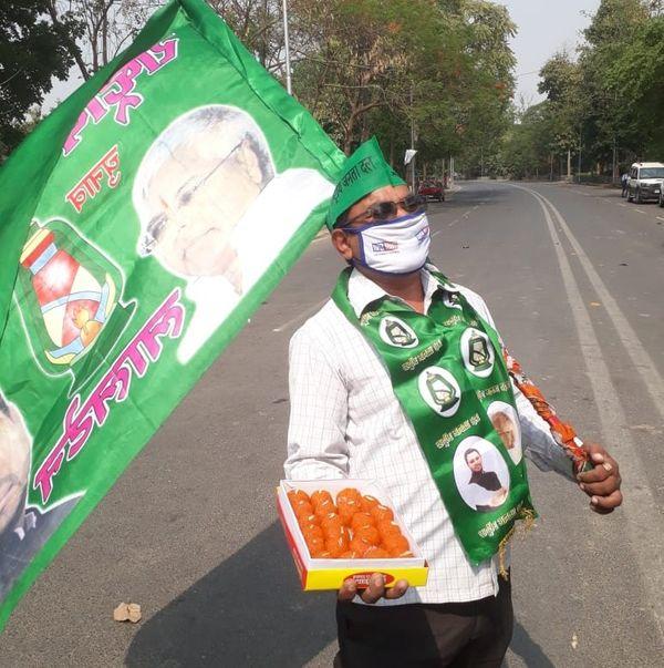 राबड़ी देवी आवास के बाहर मिठाई लिए एक कार्यकर्ता।