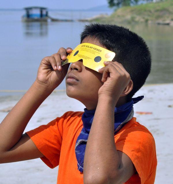 गुवाहाटी में शानदार सूर्य ग्रहण देख रहा एक बच्चा