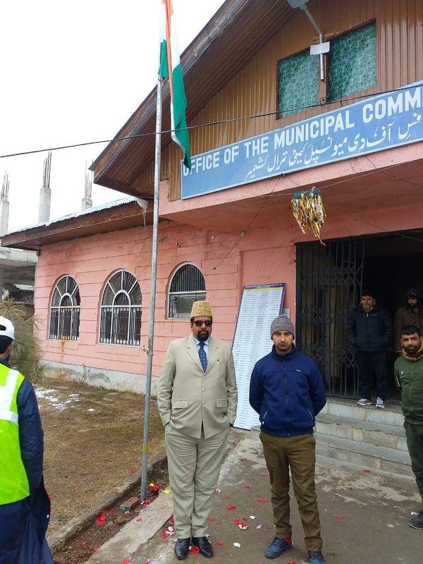 मृतक राकेश पंडित (बाएं) त्राल के नगर निगम ऑफिस में तिरंगा झंडा फहराते हुए।
