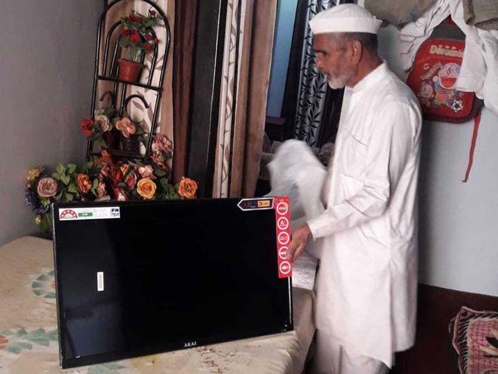 घर में डिब्बे के अंदर पैक करके रखे गए टीवी को दिखाते हुए मजाहिर। - Dainik Bhaskar