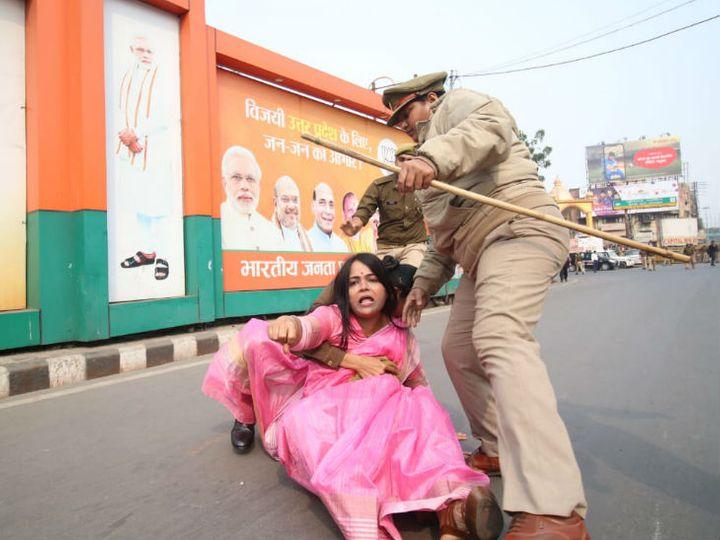 भाजपा मुख्यालय के बाहर प्रदर्शन कर रही महिला को जबरन उठाती पुलिस अधिकारी। - Dainik Bhaskar