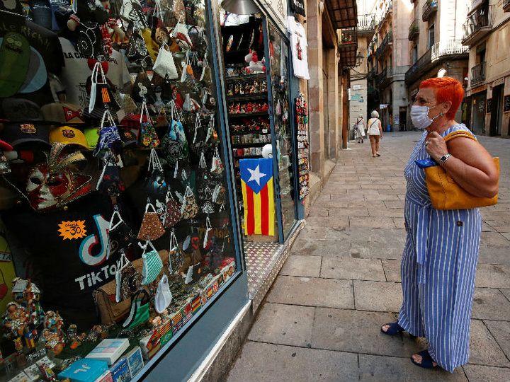 फोटो स्पेन के बार्सिलोना की है। एक बुुजुर्ग महिला सड़क किनारे एक दुकान में मास्क देख रही है। देश में 3.19 लाख लोग संक्रमित हैं। - Dainik Bhaskar