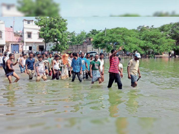 प्रदेश के 16 जिले बाढ़ प्रभावित हैं। मुजफ्फरपुर के सकरा प्रखंड का भठंडी गांव भी चाराें तरफ से बाढ़ के पानी से घिर गया है। लोगों के पास आवागमन का साधन नहीं है। नाव नहीं मिलने पर मंगलवार काे दूल्हा अाैर बाराती पैदल ही बाढ़ का पानी पार कर शादी के लिए निकल पड़े। - Dainik Bhaskar