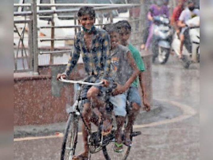 हिसार के कैंप चौक पर बारिश के दौरान साइकिल सवार बच्चे गुजरते हुए। कुछ हद तक तापमान में आई गिरावट। - Dainik Bhaskar