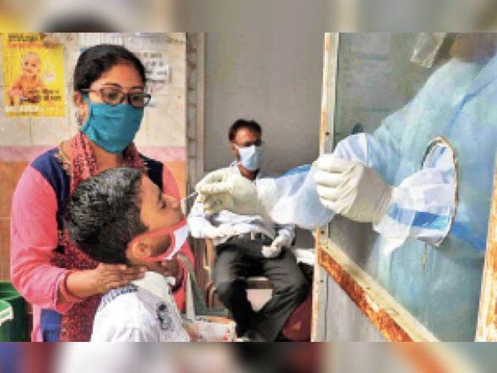 सदर अस्पताल में बच्चे का सैंपल लेते स्वास्थ्यकर्मी। - Dainik Bhaskar