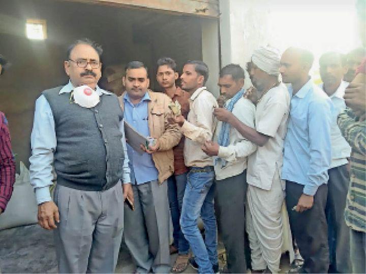 खाद बंटवाते कृषि अधिकारी। - Dainik Bhaskar