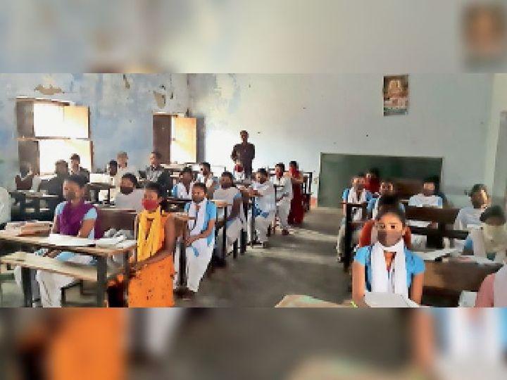 कोरोना गाइडलाइन के अनुसार सोशल डिस्टेंसिंग के लिए एक बेंच पर बैठे दो विद्यार्थी। - Dainik Bhaskar