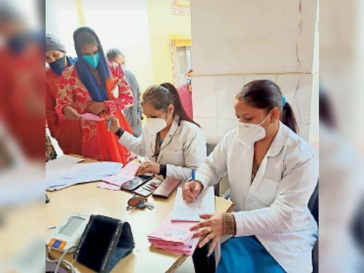 मरीजों के दस्तावेजों की जांच करते स्वास्थ्य कर्मी। - Dainik Bhaskar