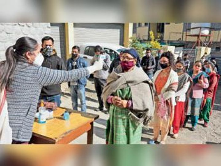 कुल्लू में निकाय चुनाव के लिए मतदान से पहले वोटरों के तापमान की जांच करती कर्मचारी। - Dainik Bhaskar