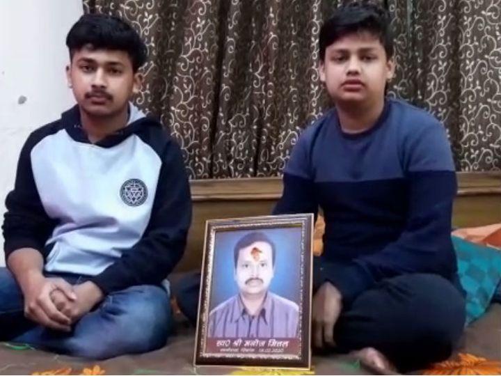 मृतक मनोज मित्तल की तस्वीर के साथ उनके बेटे। - Dainik Bhaskar