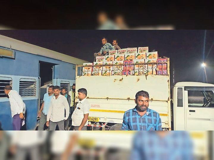 उदवाड़ा स्टेशन पर कोच में चीकू लादते श्रमिक। - Dainik Bhaskar