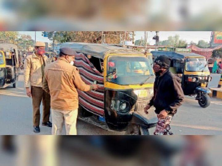 हिसार   कैंप चौक पर ऑटोरिक्शा के पर्दे हटवाते हुए सब इंस्पेक्टर खड़क सिंह। - Dainik Bhaskar