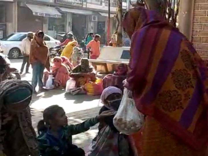 एक मंदिर के बाहर तिल से बने उत्पाद का वितरण करती एक महिला। - Dainik Bhaskar