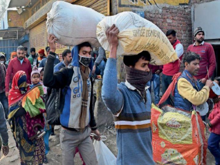 कुडली बाॅर्डर पर सिर पर सामान और गोदी में बच्चे लेकर घर लौटते मजदूर। फोटो: गोविंद सैनी - Dainik Bhaskar