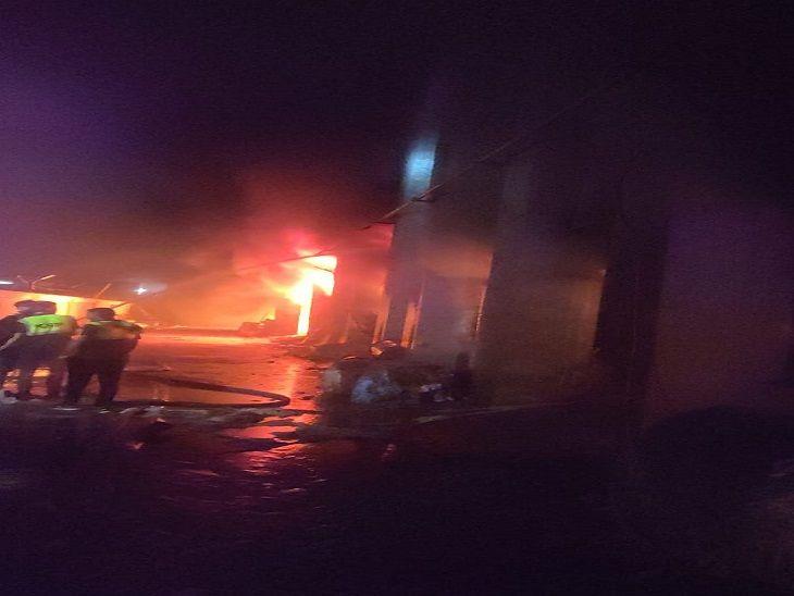 रात के समय आग को बुझाने का प्रयास करते दमकल कर्मी।