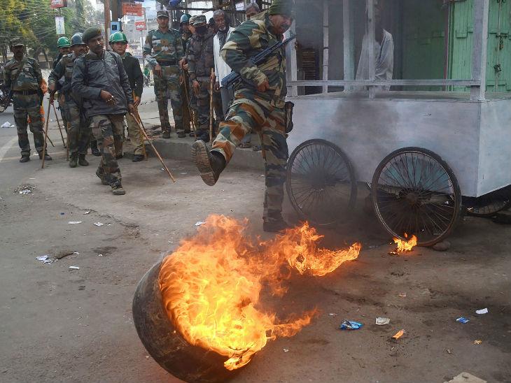 अगरतला में सुरक्षाकर्मी जलते हुए टायर को बुझाते हुए।